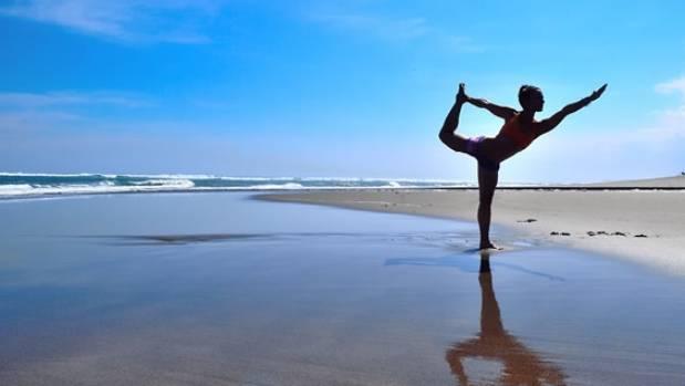 Girl doing yoga on the beach at Bali retreat