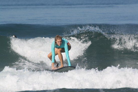 woman surfing at a womans surf retreat in bali