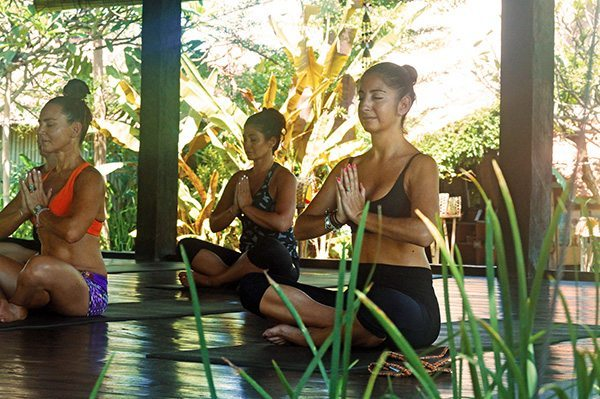 Women performing yoga in beautiful yoga shala. Yoga for all levels in Bali.