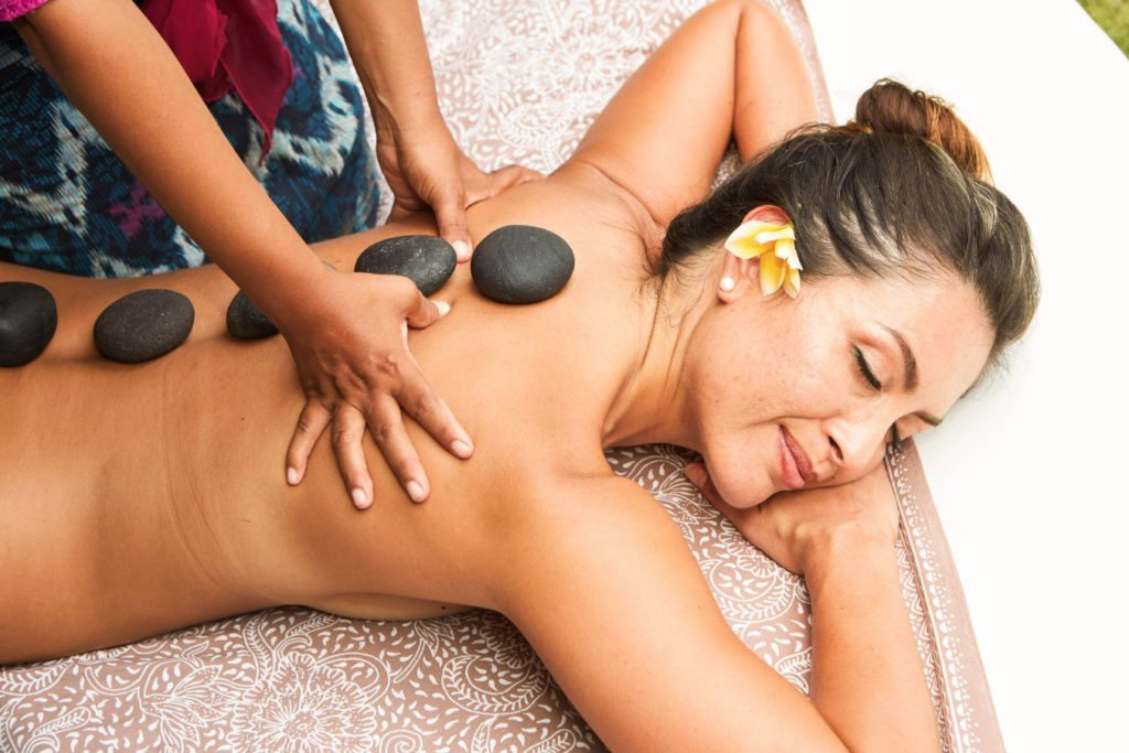 Woman enjoying a massage - More than just a wellbeing retreat. Enjoy unlimited spa treatments with our personally trained staff like hot stone massage