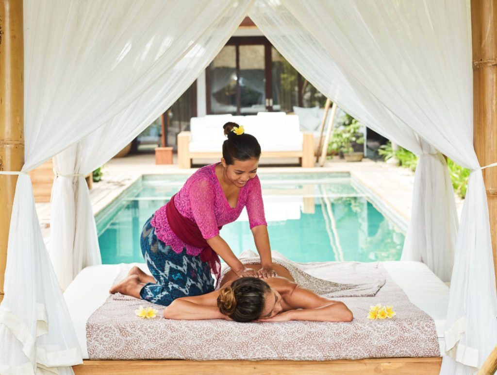 Woman enjoying a massage by the pool at our gorgeous Bliss yoga and wellness retreat
