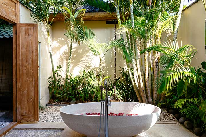 Stunning luxury outdoor bathroom with stone bath and rose petals, Bali retreat, Bliss Sanctuary For Women, Seminyak Sanctuary