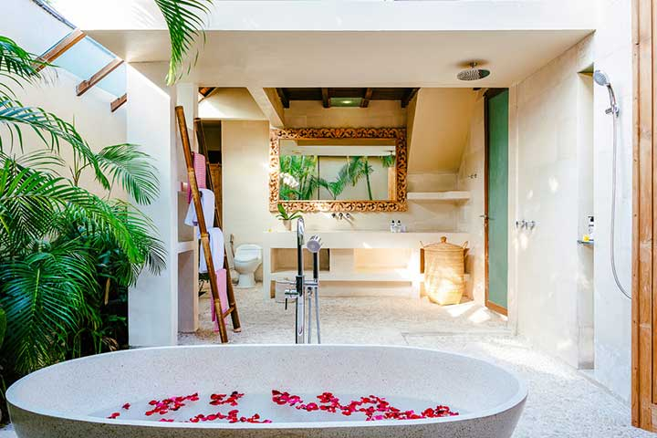 Stunning luxury indoor/outdoor bathroom with stone bath and rose petals, Bali retreat, Bliss Sanctuary For Women, Seminyak Sanctuary