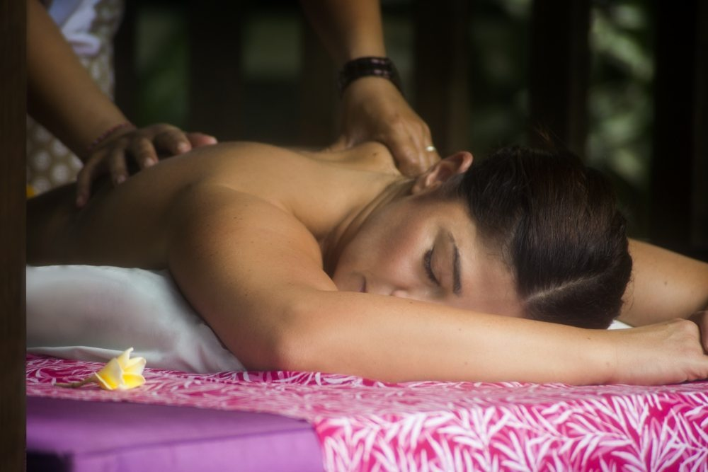 A guest enjoying a blissful massage - indulge in unlimited spa treatments by our beautiful pool in our luxurious massage shala