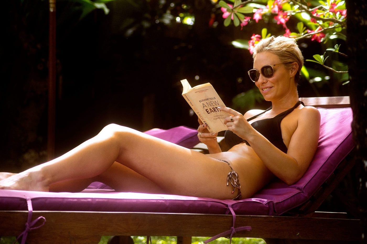 Woman relaxing reading a book and sunbathing in Bali at Bliss Sanctuary for Women