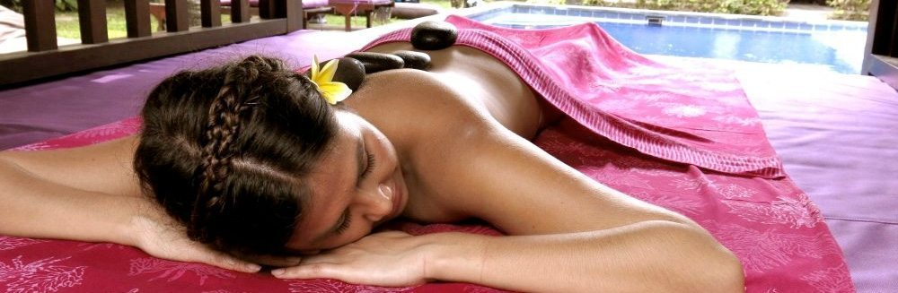 Woman enjoying relaxing stone massage by the Sanctuary pool