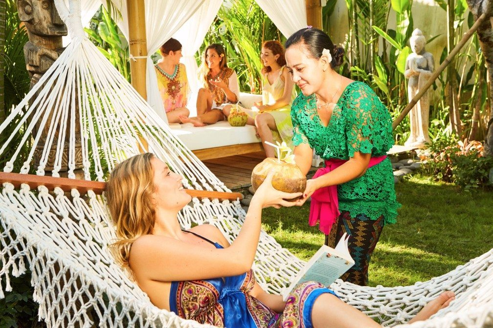 Woman in hammock, reading with hostess providing coconut at Bliss Sanctuary Bali