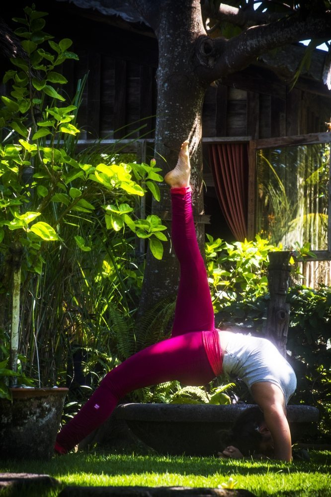 Woman performing yoga in beautiful Bliss gardens