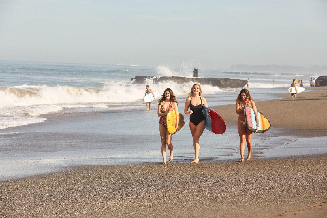 Women walking along beautiful Bali beach with surf boards on Retreat Surf Package