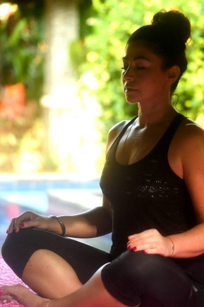 Woman meditating in the beautiful outdoor day bed at Bliss Sanctuary
