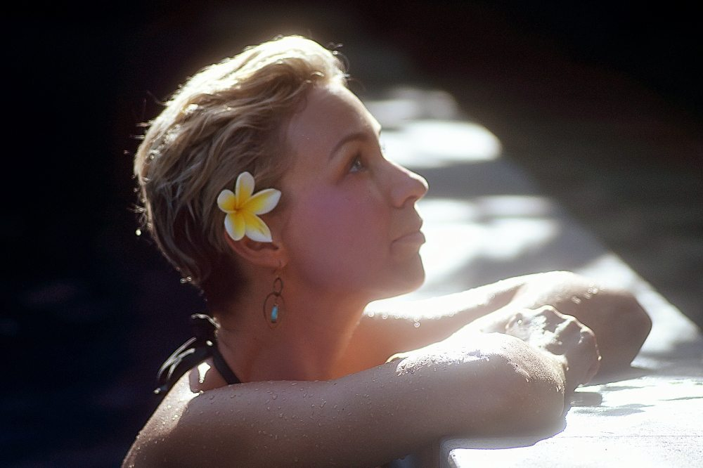 Woman with flower in her hair relaxing in Bliss Sanctuary pool