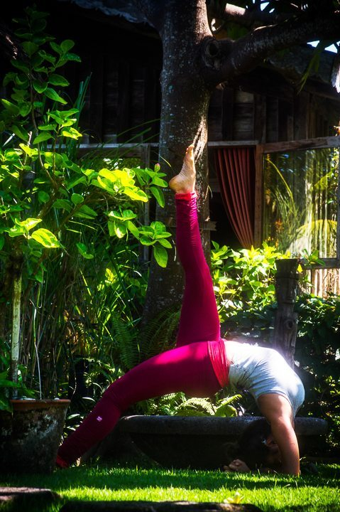 Woman in yoga pose in beautiful lush green surroundings at Bliss wellness yoga retreat in Bali