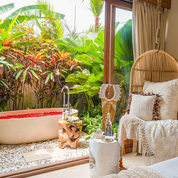 Hanging chair overlooks gorgeous outdoor rose petal stone bath in Bali retreat, Garden Bath Retreat Room, Bliss Sanctuary For Women, Canggu