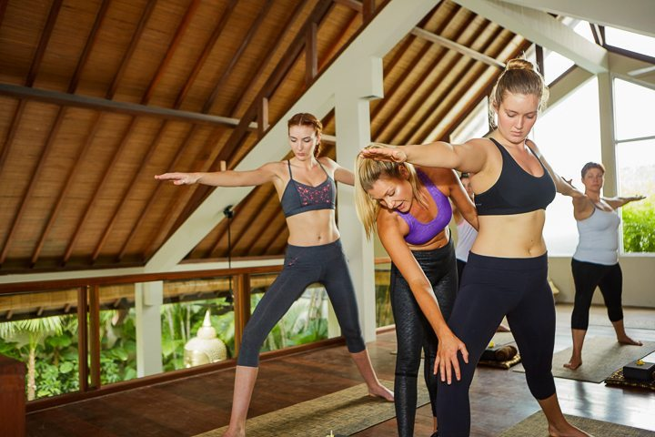 Women stretch in yoga class at Bliss yoga and spa retreat in Bali - with us yoga classes are unlimited