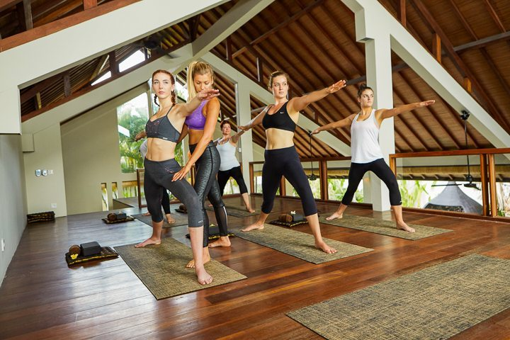Yoga instructor with women students, doing yoga class in beautiful shala at our Bliss Bali yoga and spa retreat