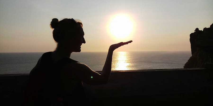 Silhouette of girl at gorgeous sunset at Uluwatu Temple Bali