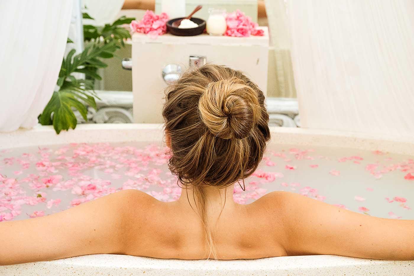 Woman relaxing in flower bath at Bali wellness retreat