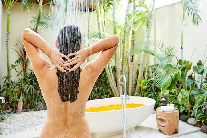solo holiday - woman enjoying luxury outdoor shower