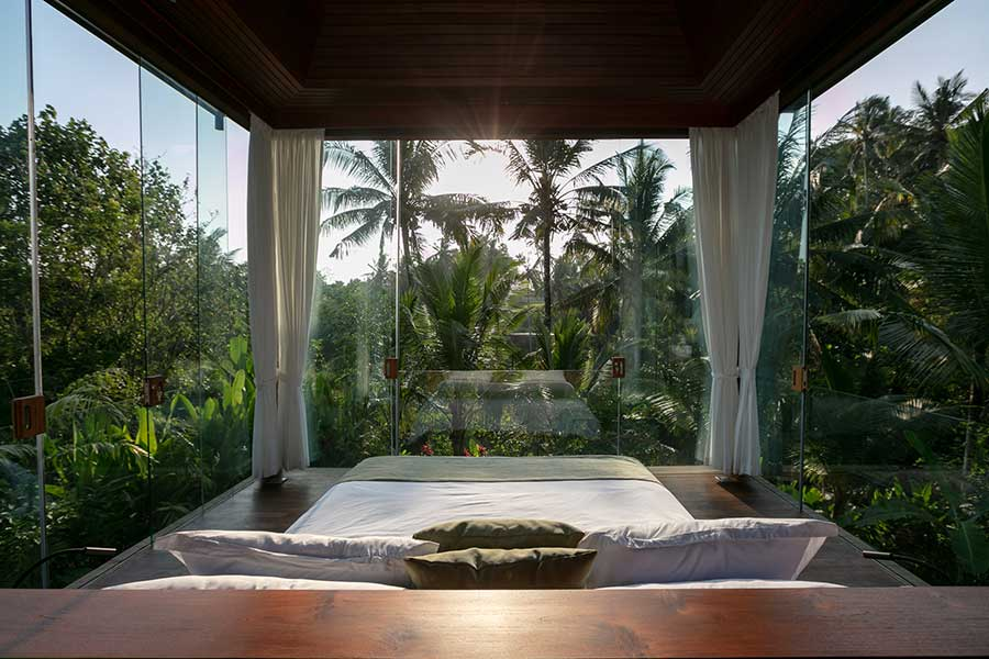 Beautiful garden setting glass walls bedroom in Ubud Bali resort