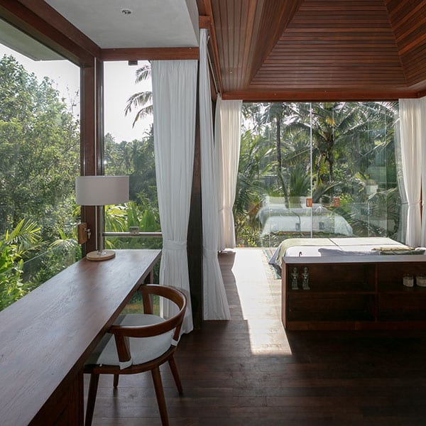 Stunning bedroom in rainforest setting with glass walls in luxury Bali Retreat
