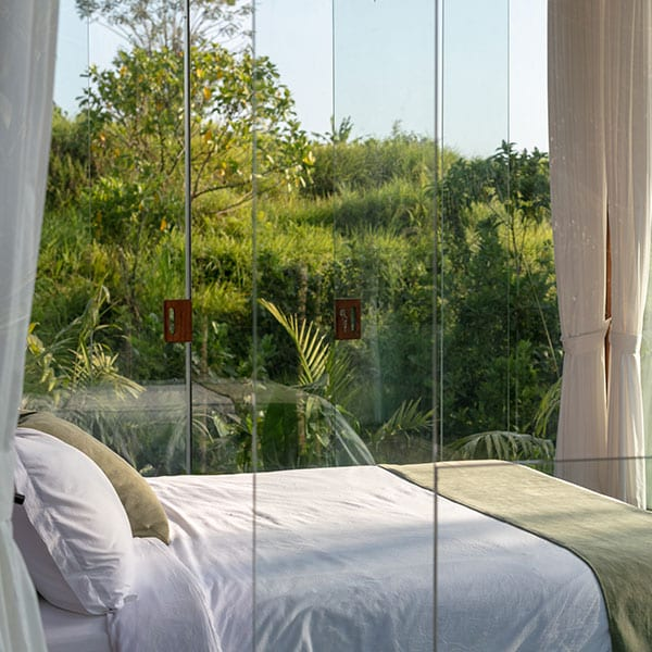 Bedroom surrounded by glass with rainforest view in Bali Retreat
