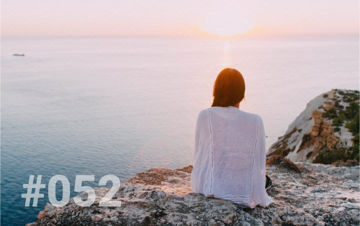A young woman wearing a white shawl. She is sitting on a cliff edge watching the sun set over the ocean