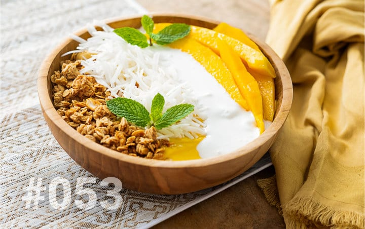 Delicious smoothie in a wooden bowl with muesli, sliced mango, shredded coconut and mint leaves