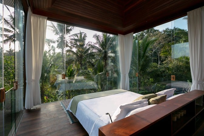 bedroom with glass walls overlooking tropical garden at the Ubud Bliss Sanctuary, Bali