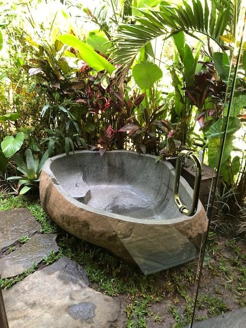 An outdoor oval stone bath surrounded by tropical plants