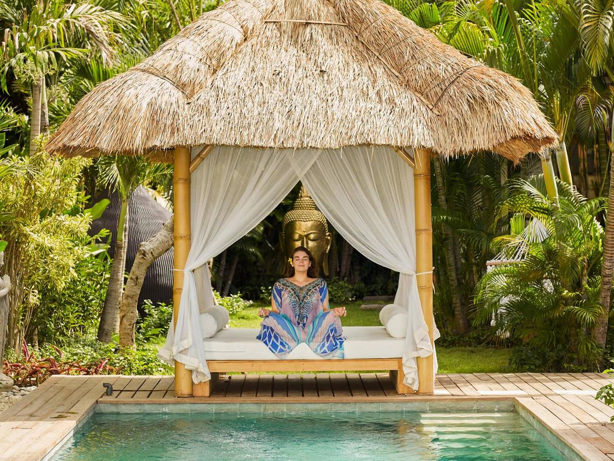 A woman meditates under a small bamboo and grass shelter. It is positioned in front of a swimming pool within a tropical garden.