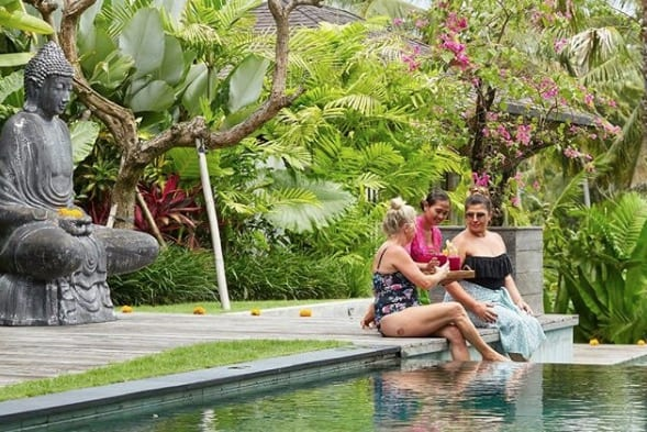 Guests enjoy drinks by the pool Bliss Bali retreat