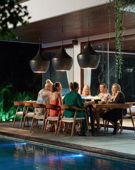 Guests enjoying dinner by the pool Bali retreat Ubud