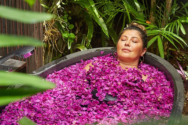 Woman relaxing in flower bath Bliss Bali retreat