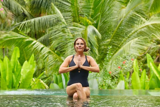 Woman relaxing and meditating in beautiful pool in Bali