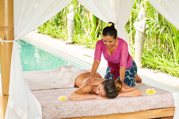 Woman receiving luxury massage by the pool at Bliss Sanctuary for Women