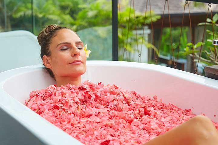 Woman relaxing in flower bath at Bliss Bali retreat