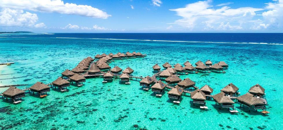 Beach travel vacation Tahiti hotel overwater bungalows luxury resort in coral reef lagoon ocean. Moorea, French Polynesia, Tahiti, South Pacific Ocean.